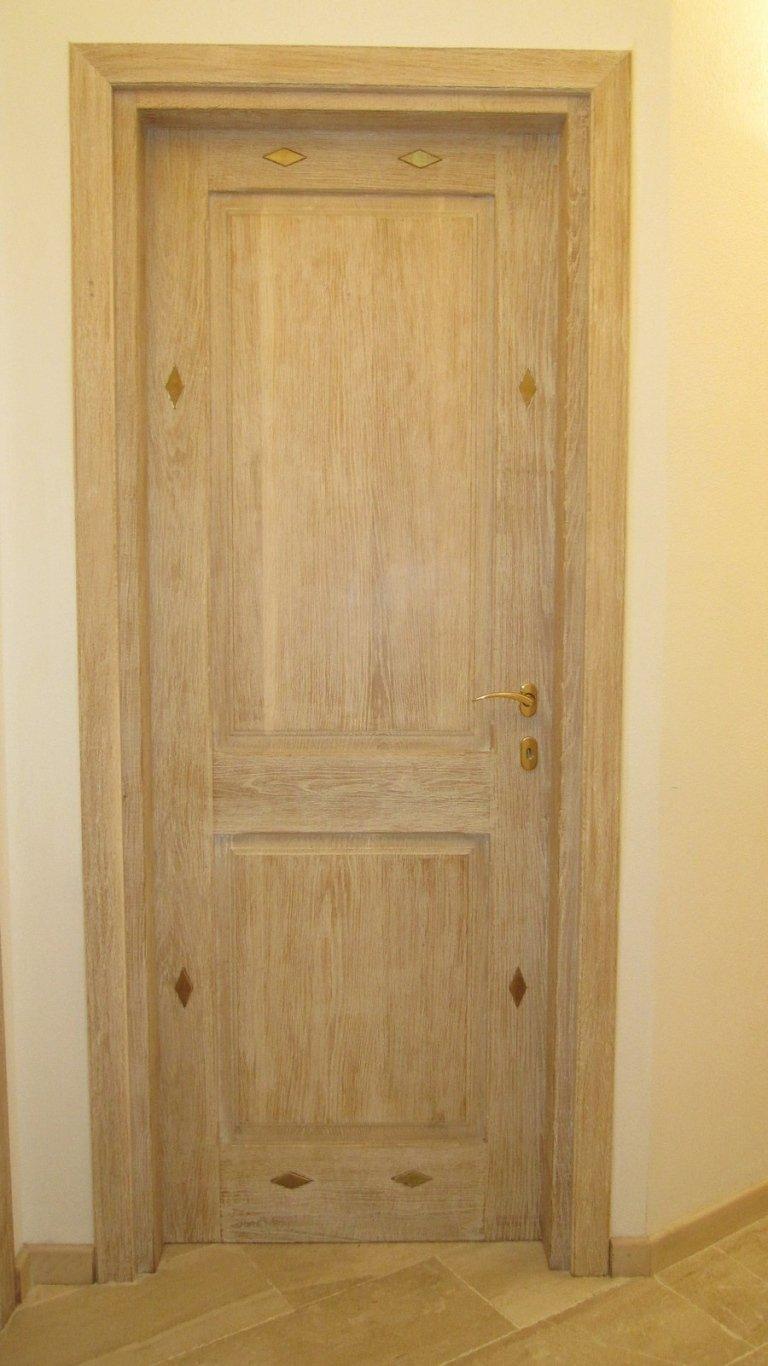 Porta in legno chiaro con decorazioni a rombi