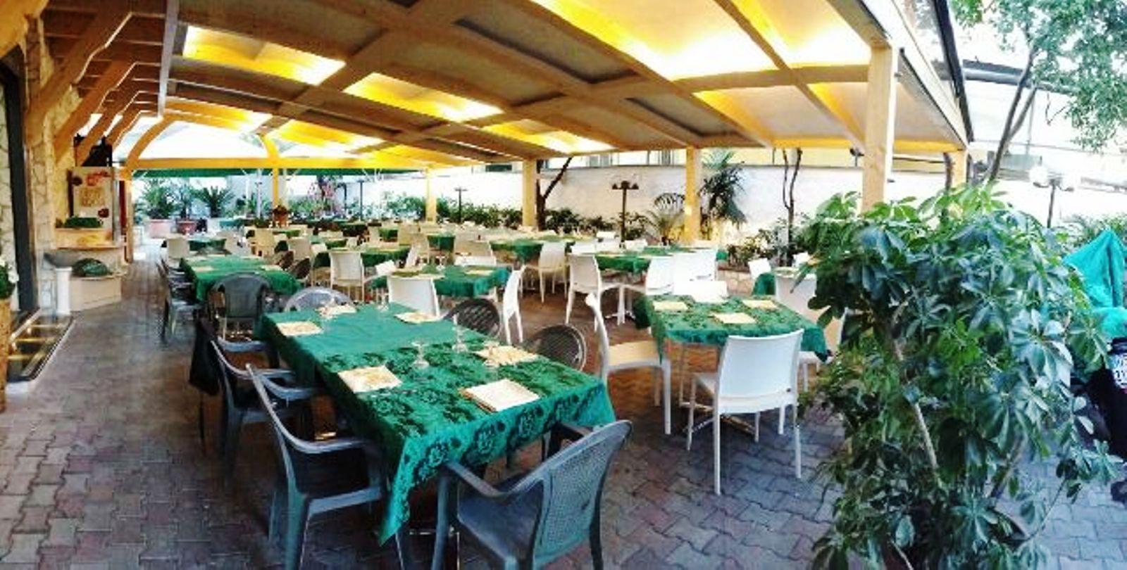dei tavoli apparecchiati con tovaglie verdi all'esterno di un ristorante sotto una tettoia in legno