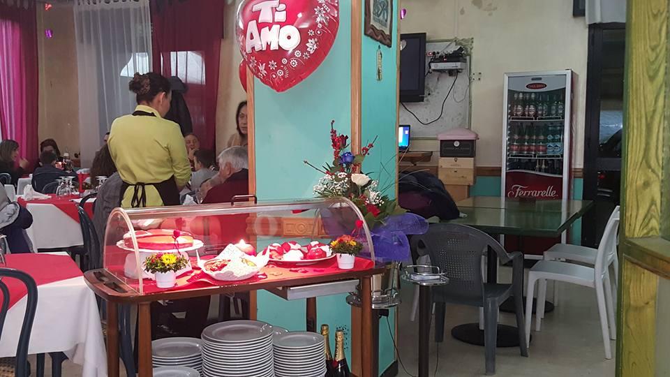 interno del ristorante con delle persone sedute ai tavoli, una cameriera in piedi e un carrellino con deli dolci e sotto dei piatti