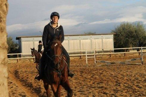 un ragazzo a cavallo nel maneggio