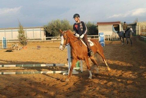 un ragazzo con un caschetto su un cavallo marrone