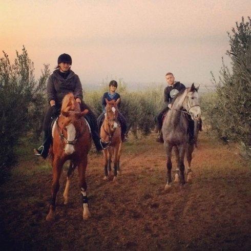 due ragazze e un ragazzo a cavallo nella campagna