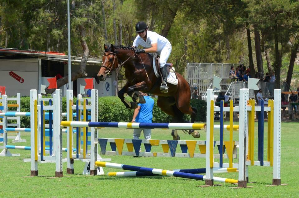 fantino a cavallo che salta un ostacolo giallo e blu