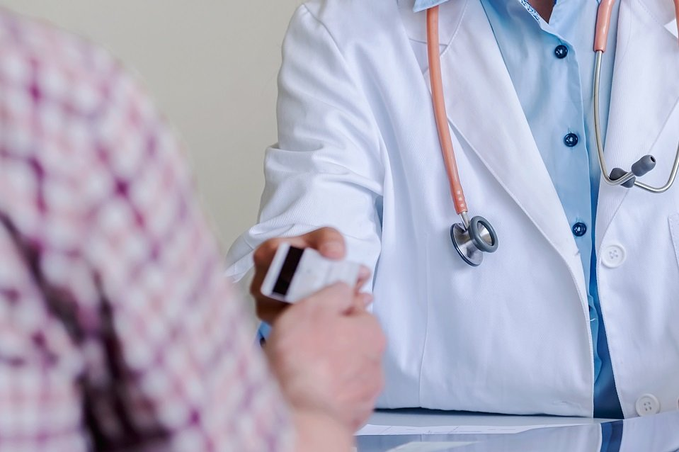 Medico consegna tessera sanitaria a paziente