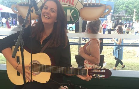 lady smiling playing a guitar