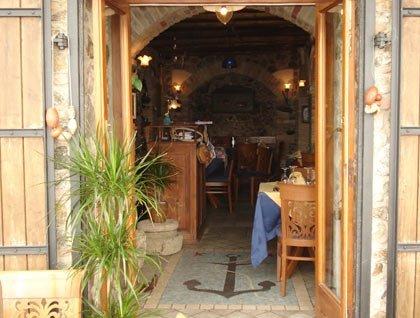Vista da fuori dell'interno del ristorante con tavoli e sedie in legno