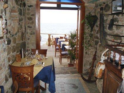 Un tavolo apparecchiato con due sedie e altri tavoli su un terrazzo vista mare