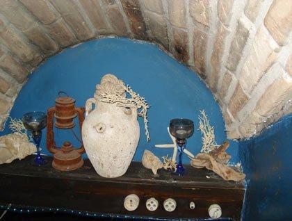 Dei vasi, conchiglie e bicchieri su un mobile