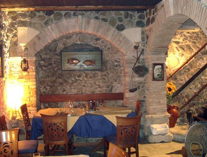 Un tavolo apparecchiato con una tovaglia gialla e blu in un ristorante con muri in pietra