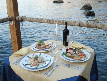 Un tavolo apparecchiato con dei piatti a base di pesce e vista del mare
