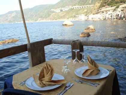 tavolo apparecchiato e vista del mare con gli scogli