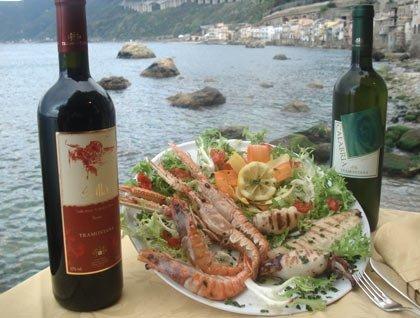 Un piatto a base di pesce alla griglia, scampi e due bottiglie di vino