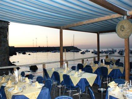 tavoli apparecchiati sotto una copertura all'esterno del ristorante vista mare