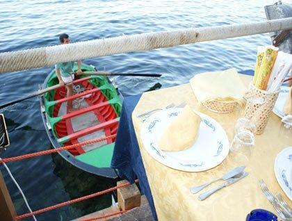 Un tavolo apparecchiato e sotto un ragazzo in barca che rema