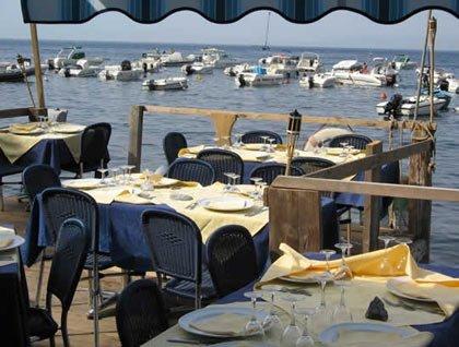 Di tavoli apparecchiati all'esterno del ristorante e vista delle barche in mare