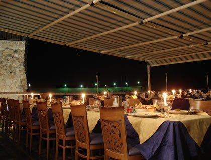 Dei tavoli apparecchiati con delle candele sotto una copertura all'esterno del ristorante