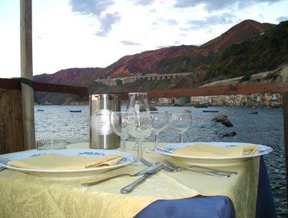 Un tavolo apparecchiato con dei bicchieri e vista del mare e delle montagne