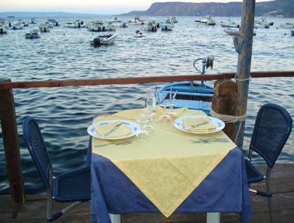 Un tavolo apparecchiato con una tovaglia gialla e blu e vista delle barche in mare