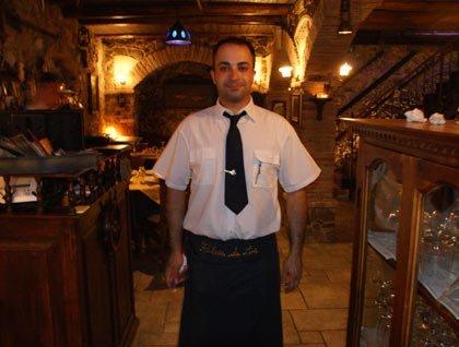 Un cameriere con una camicia bianca e una cravatta nera