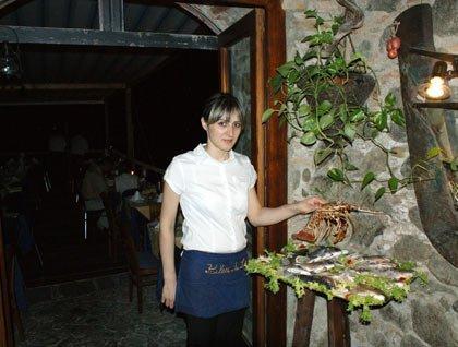 Una cameriera con in mano un astice e accanto un vassoio con dei pesci
