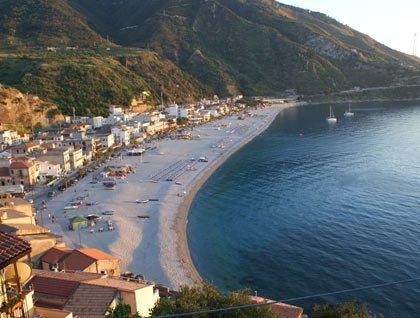 Vista dall'alto di mare, spiaggia, un paesino e delle montagne