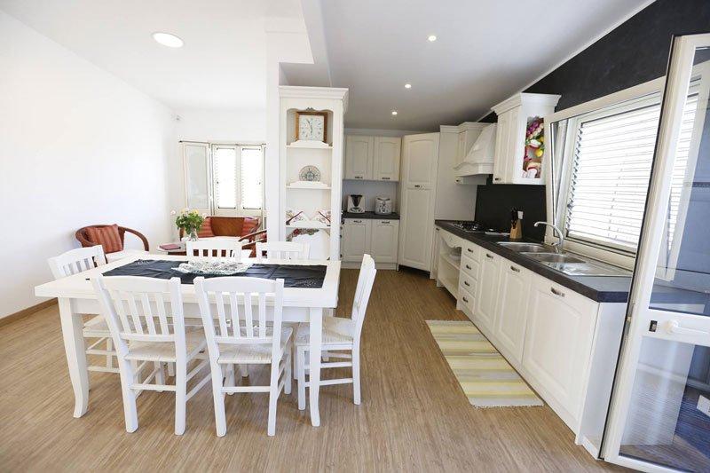 una cucina moderna con sulla sinistra un tavolo con sei sedie,sulla destra il lavabo con il piano da lavoro e i fornelli e in fondo un  altro mobile angolare che completa la cucina