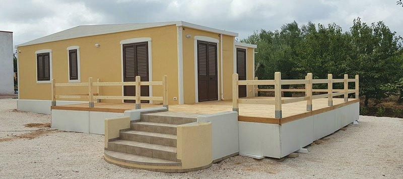 una piccola costruzione di color giallo con serramenti di color marrone, un terrazzino con dei parapetti in legno chiaro e 4 gradini in marmo color beige