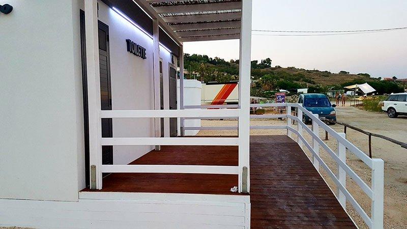 una costruzione in legno lucido di color  bordeaux e bianco con sulla sinistra due porte d'entrata con scritto Toilette