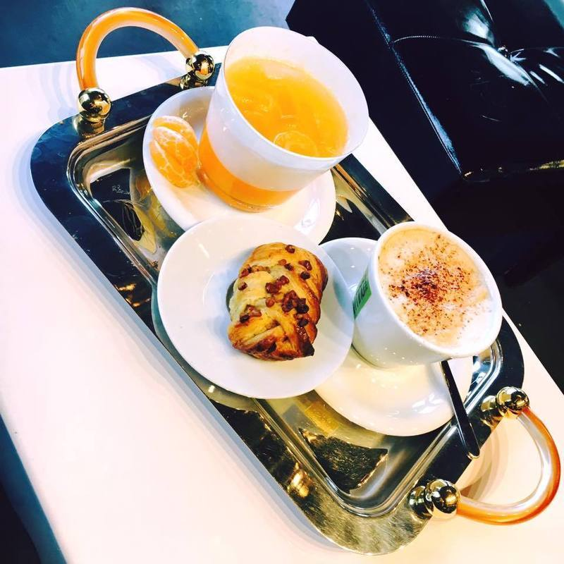 un vassoio con una tazza di cappuccino spremuta e un pasticcino