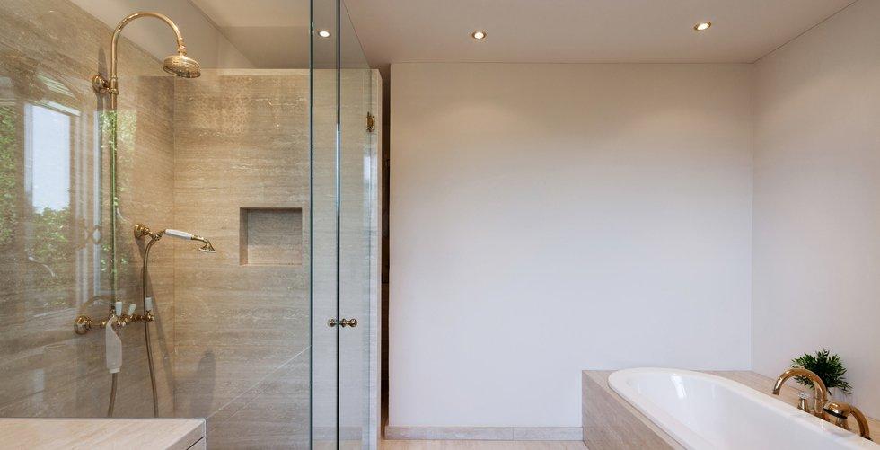 bagno moderno con box doccia in vetro, lavabo, rubinetteria e arredo bagno