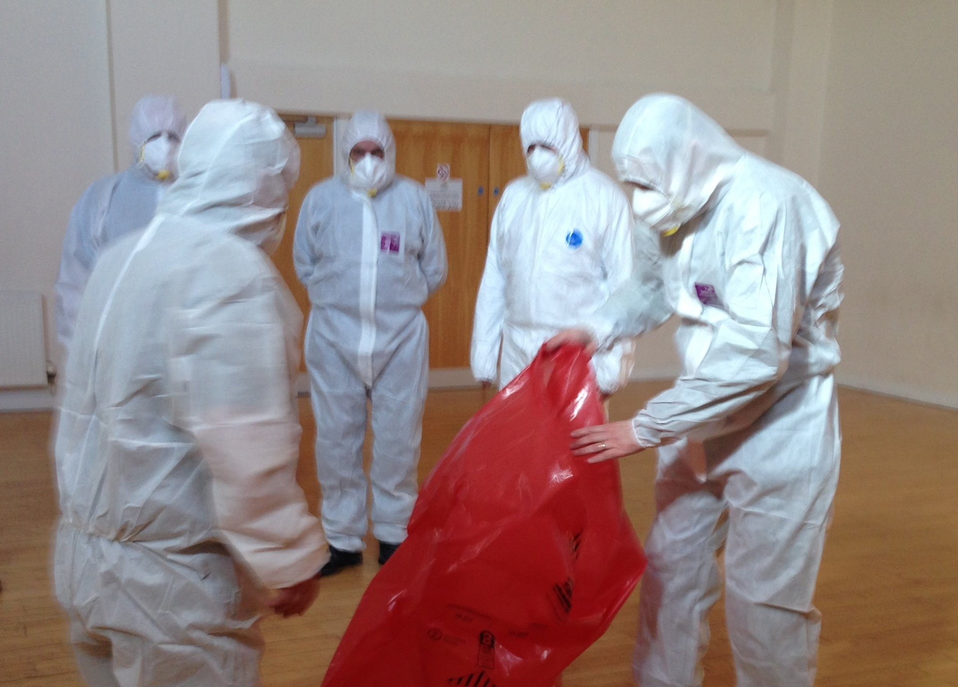 Training participants wearing white protection suits