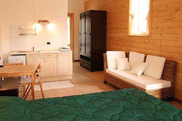 una camera con un letto, un divano e un cucinotto