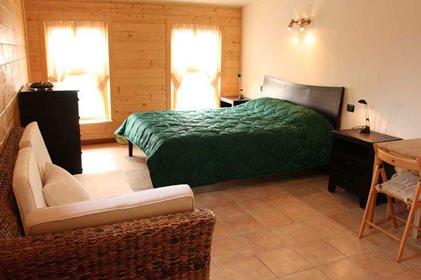 Una camera con un letto matrimoniale con dei comodini e un como davanti