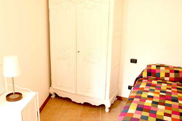 un letto e sulla destra un mobile di color bianco