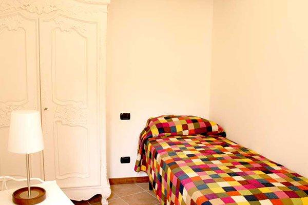 una camera con un letto singolo e accanto un armadio di color bianco
