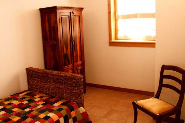 una camera con letto singolo e un armadio in legno