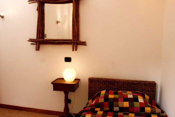un letto singolo, accanto un comodino e uno specchio al muro