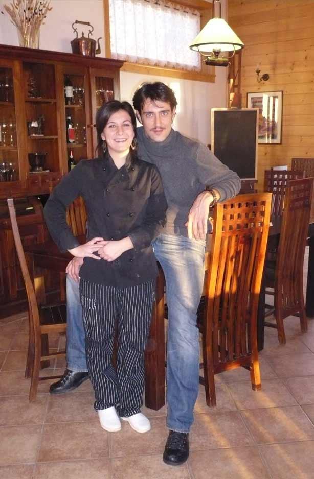 un uomo seduto su un tavolo e accanto una donna