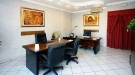 ufficio con scrivania e sedie, tende rosse sullo sfondo