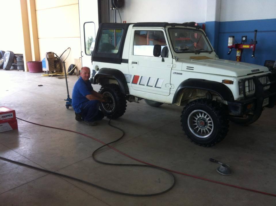 Un meccanico controlla gli pneumatici di una jeep bianca