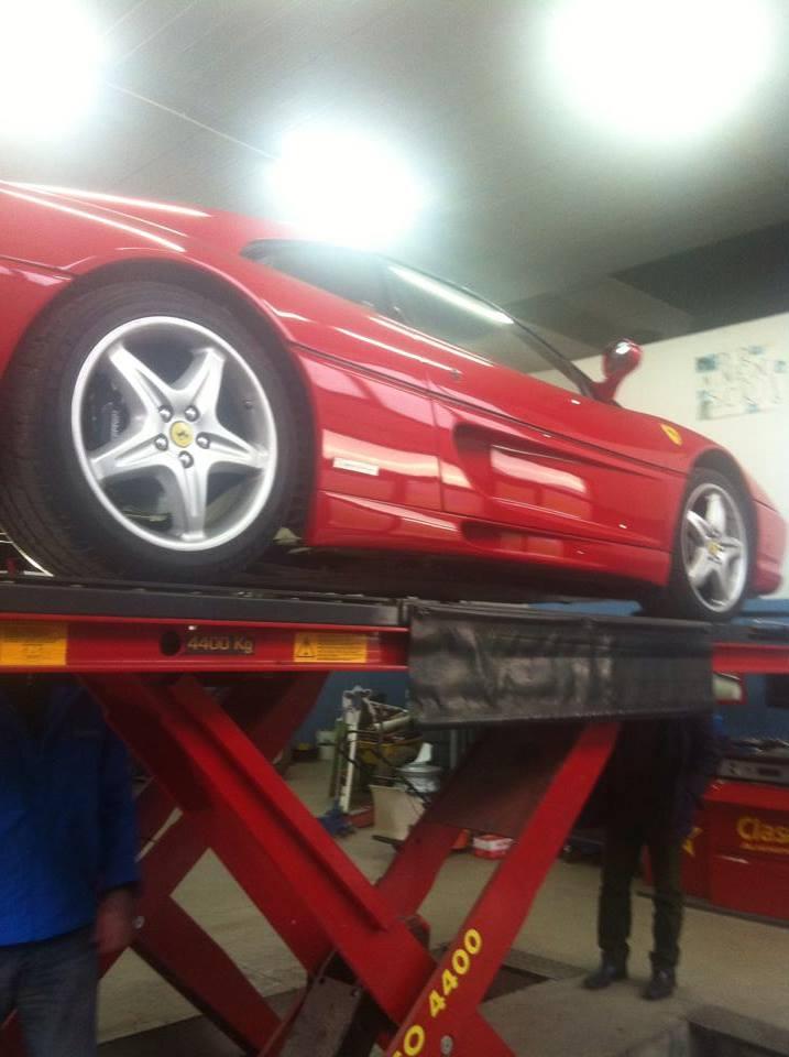 Vista laterale di una Ferrari sulla piattaforma elevatrice