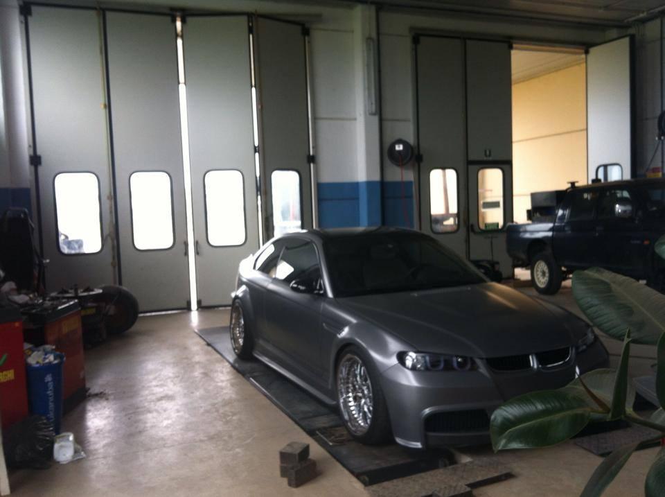 Un'auto grigia in riparazione nell'officina