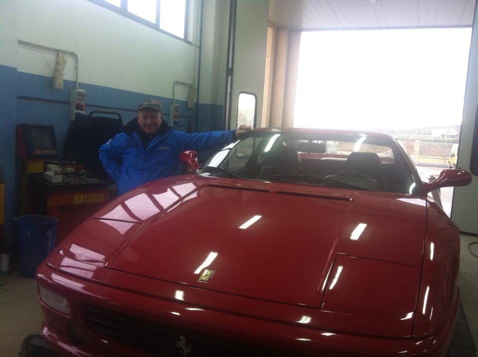 Meccanico in posa a fianco di una Ferrari