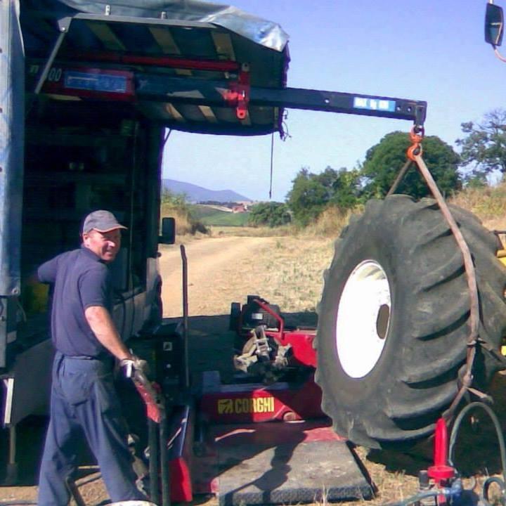 un uomo sta utilizzando un macchinario con un braccio per sollevare un pneumatico assicurato da una catena