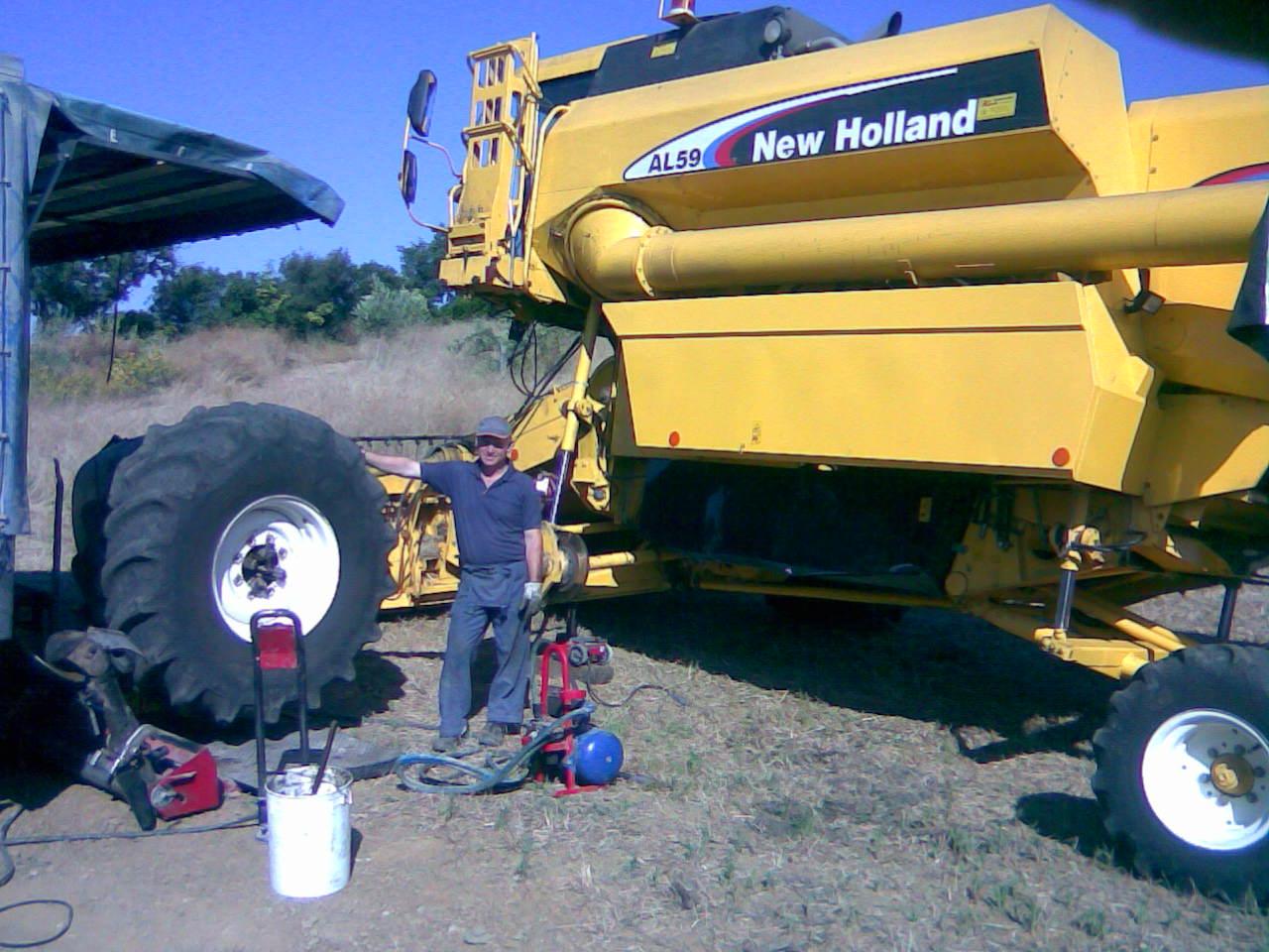 Un meccanico in posa vicino allo pneumatico di una mototrebbia