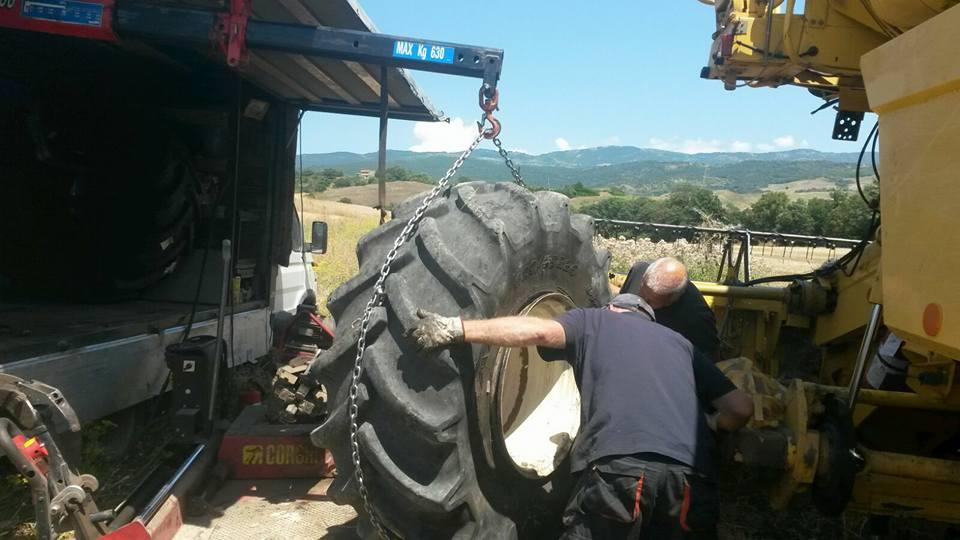un uomo sposta un grande pneumatico assicurato da una catena