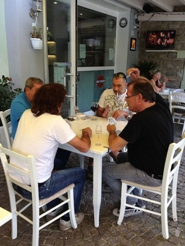 quattro signori seduti al tavolo di un ristorante