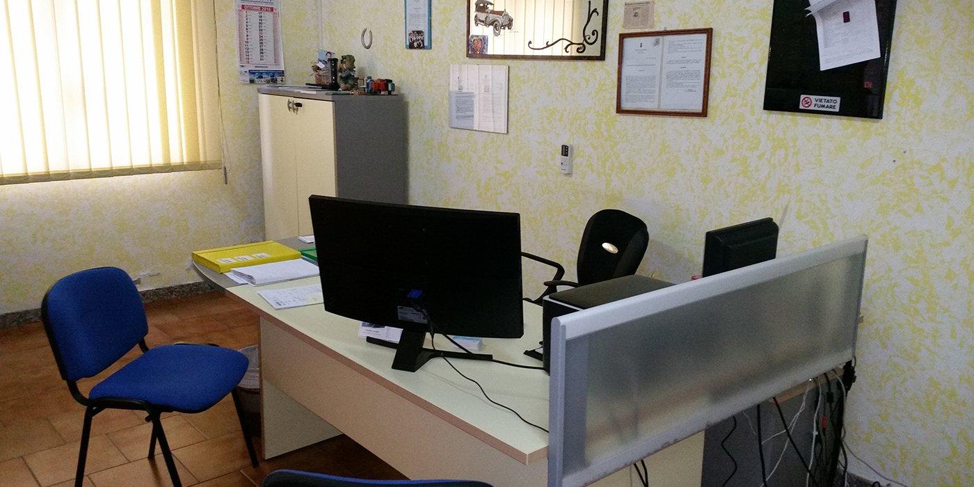 Ufficio dell'autoscuola con scrivania e sedie