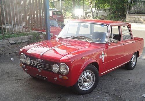 un'Alfa Romeo Giulietta di color rosso vecchio modello