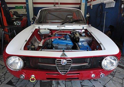 un'Alfa Romeo bianca e rossa senza cofano con vista del motore